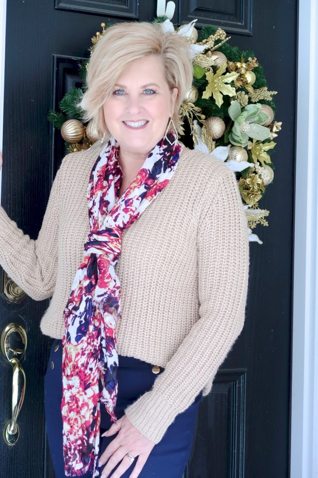 A gold sweater and a printed scarf worn by Fashion Blogger 50 Is Not Old