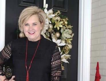 Fashion Blogger 50 Is Not Old wearing a black lace top and a vintage red tassel necklace