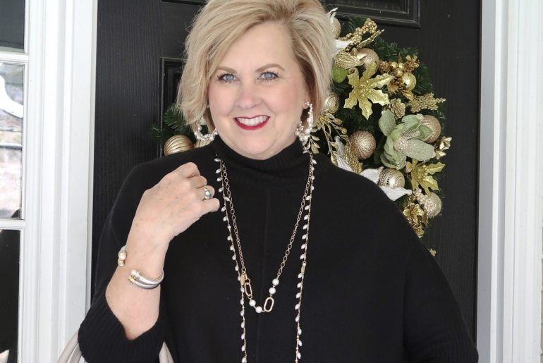 Fashion Blogger 50 Is Not Old wearing a black poncho sweater with pearls