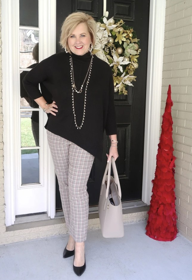 Fashion Blogger 50 Is Not Old wearing a black poncho sweater and plaid pants