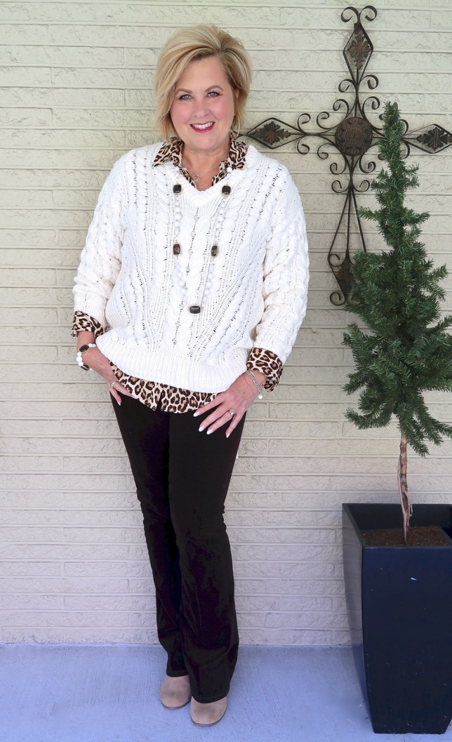 Fashion Blogger 50 Is Not Old wearing an ivory cable knit sweater with a leopard print shirt