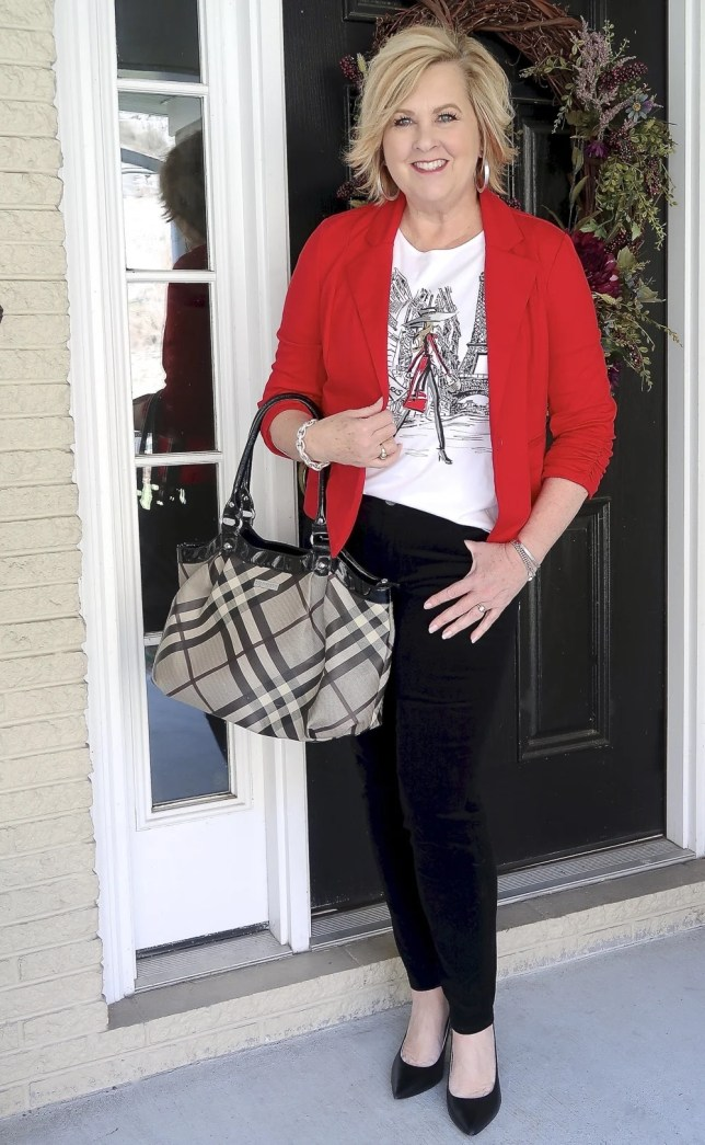 Fashion Blogger 50 Is Not Old looks stylish in a graphic tee, black pants, and a red jacket