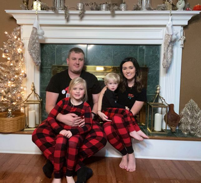 family in pajamas in front of fireplace