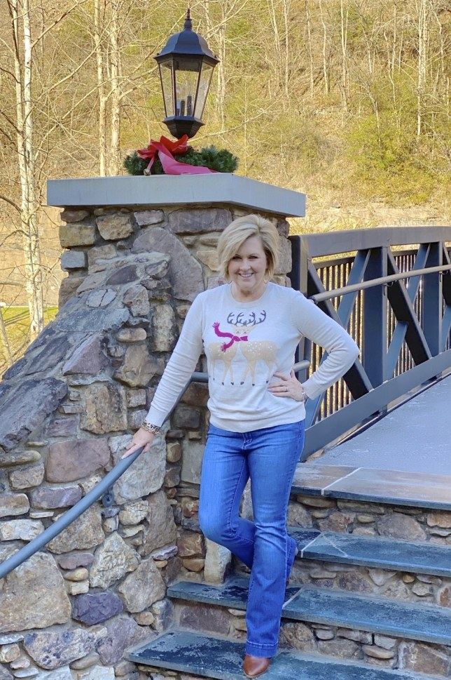 50 Is Not Old Fashion Blogger wearing a Holiday sweater on steps to a bridge