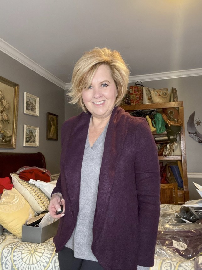 Fashion Blogger 50 Is Not Old holds a try on session with a deep violet shawl cardigan