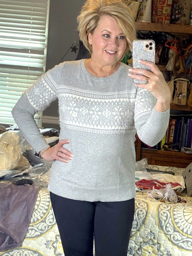 Fashion Blogger 50 Is Not Old holds a try on session with a gray Fairisle sweater