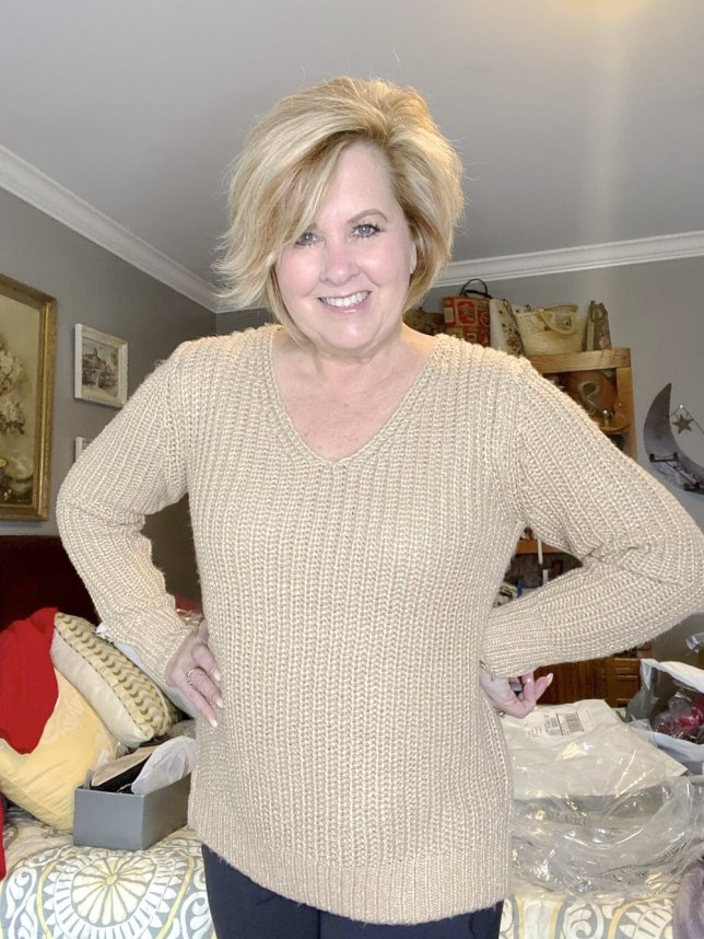 Fashion Blogger 50 Is Not Old holds a try on session with a gold sweater with a metallic thread