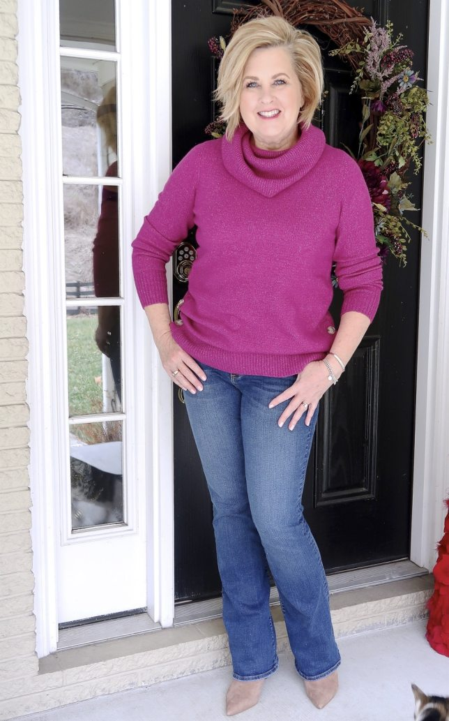 Fashion Blogger 50 Is Not Old wearing a bright fuchsia sweater with flare jeans