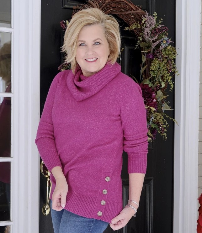 Fashion Blogger 50 Is Not Old wearing a bright colored fuchsia sweater with side buttons and a cowl neck