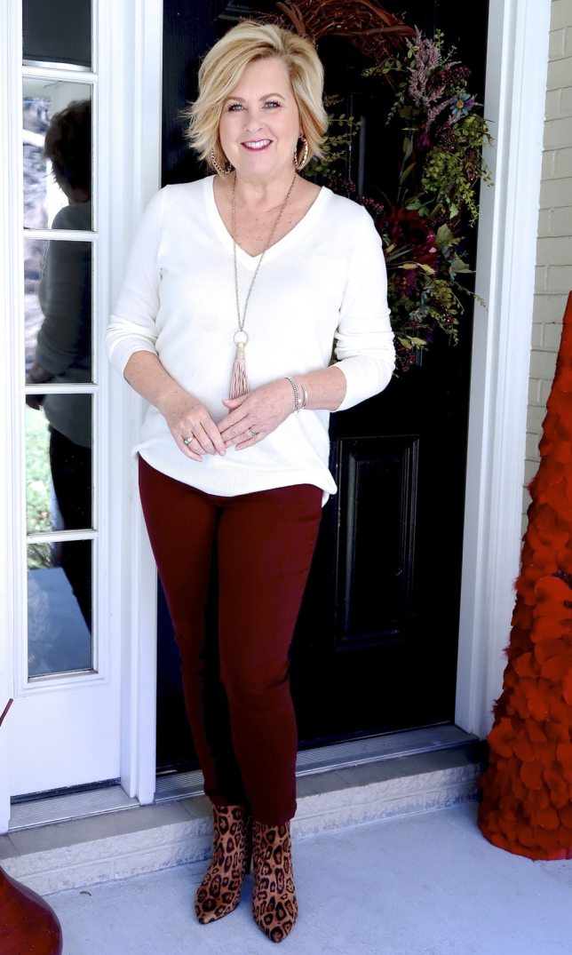 Fashion Blogger 50 Is Not Old is wearing an ivory v-neck sweater with burgundy pants.