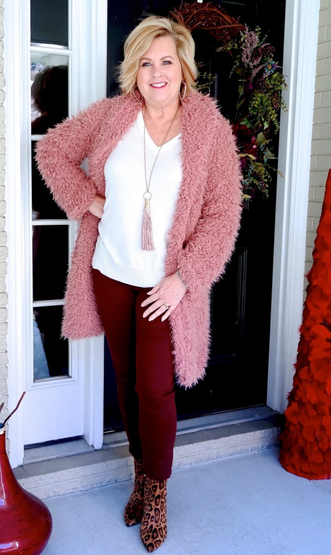 Fashion Blogger 50 Is Not Old is wearing a pink sherpa warm and cozy coat with burgundy pants and animal print booties.