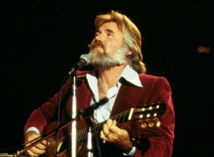 Kenny Rogers passes at 81 kenny rogers - A man playing a guiter singing into a microphone 300x220 - Kenny Rogers, legendary Country Music Icon bows out at 81