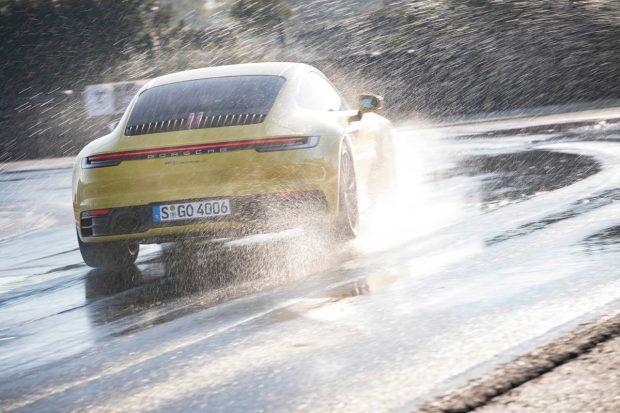 Yellow Porsche 911 seen from behind in the wet