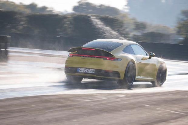 Yellow Porsche 911 driving in the wet