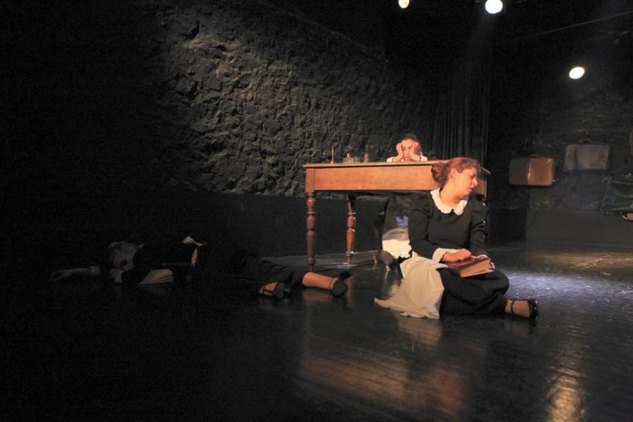 Φωτογραφία: Στη σκηνή του θεάτρου βλέπουμε τρεις καμαρίερες με μάρες στολές, άσπρες ποδιές και άσπρο γιακά και τα μαλλιά πιασμένα πάνω. Η μία κοιμάται αριστερά στο πάτωμα πάνω στο δεξί της χέρι με χέρια και πόδια απλωμένα. Η δεύτερη κοιμάται στηριγμένη στο πόδι ενός γραφείου και η τρίτη κάθεται στο γραφείο και κρατάει το κεφάλι της. Στο βάθος βλέπουμε βαλίτσες κρεμασμένες στον τοίχο.