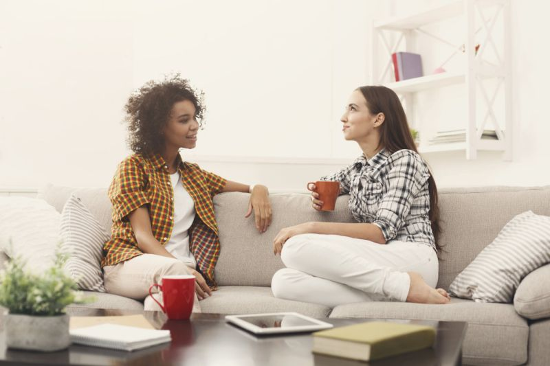 two women sitting and talking over problems drinking coffee on a couch relaxed