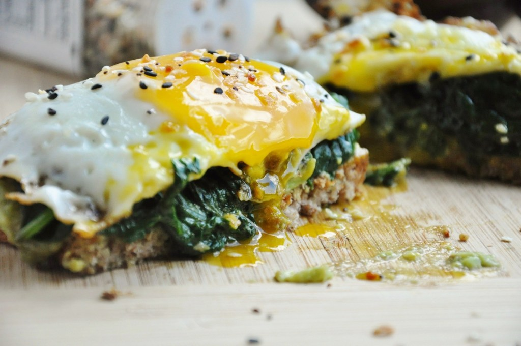 avocado toast with sautéed spinach a sunny side up egg is cut in half and the juices are running out of the toast
