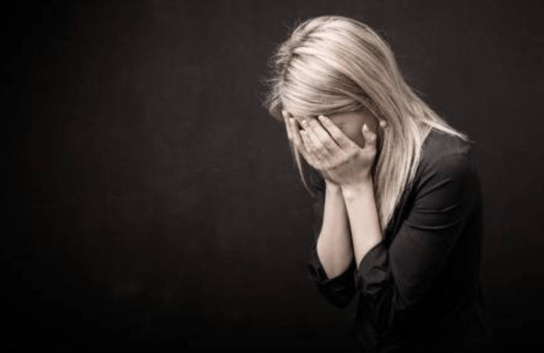A blond woman with her head bent down into the palm of her hand weeping