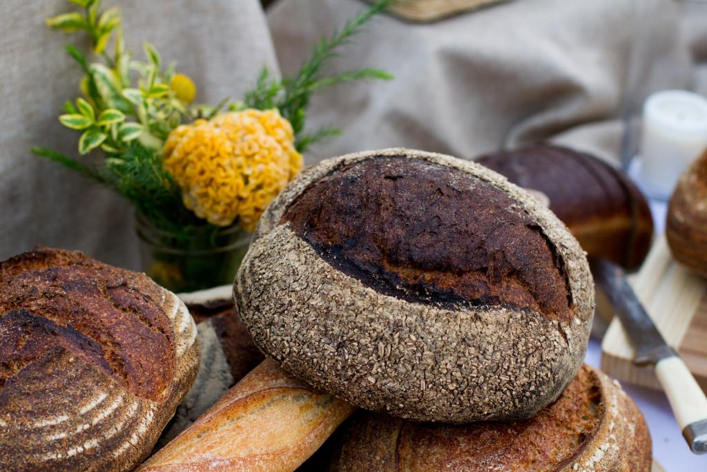 Artisan bread displayed on a table with linen rises in the background and yellow flowers in a vase