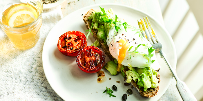 avocado toast with chopped avocado and a poached egg that is dripping the yellow runny yolk on to the place with two cherry tomatoes cut in half and topped with crushed pepper corns sitting and a table with white linen and a glass of lemonade
