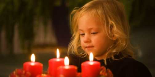 young child looking at 4 lit candles in a dark room