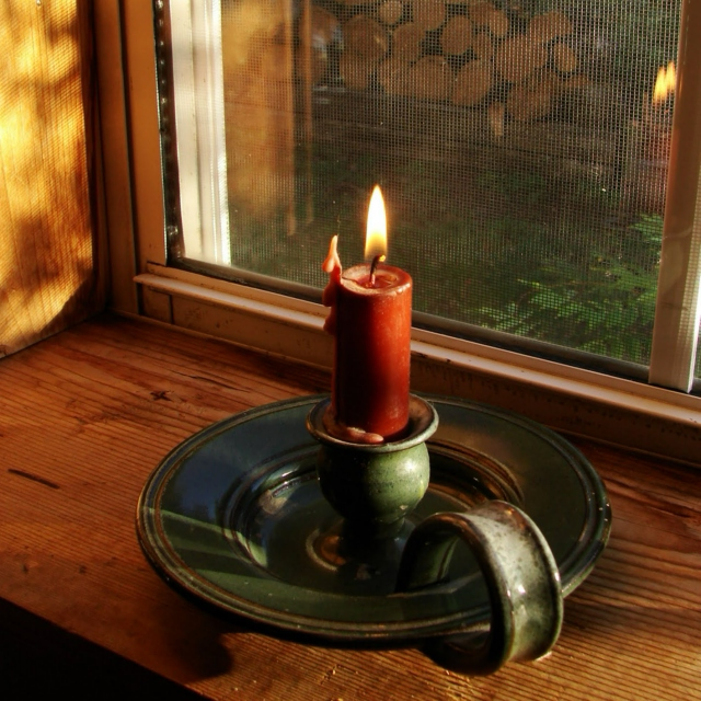 a red candle in an old-fashioned green metal holder lit and sitting in a window sill