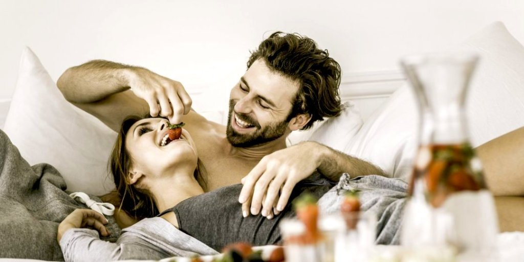 Man and woman in bed, he's feeding her strawberries, they are laughing and she's laying her head on his stomach to show attentive, caring over the top win