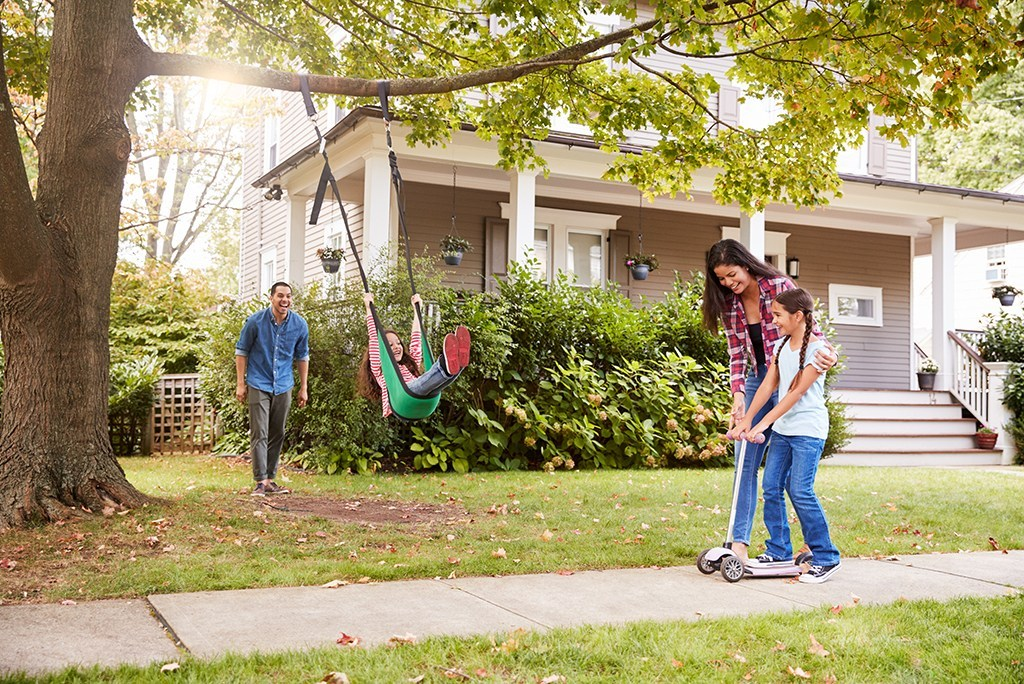 American basic needs to be happy, shows a family playing in the yard of a middle class neighborhood