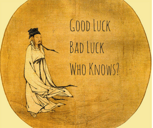 a yellow and orange baiting with a picture of a Chinese man in a robe, the words say, Good luck bad luck who knows?