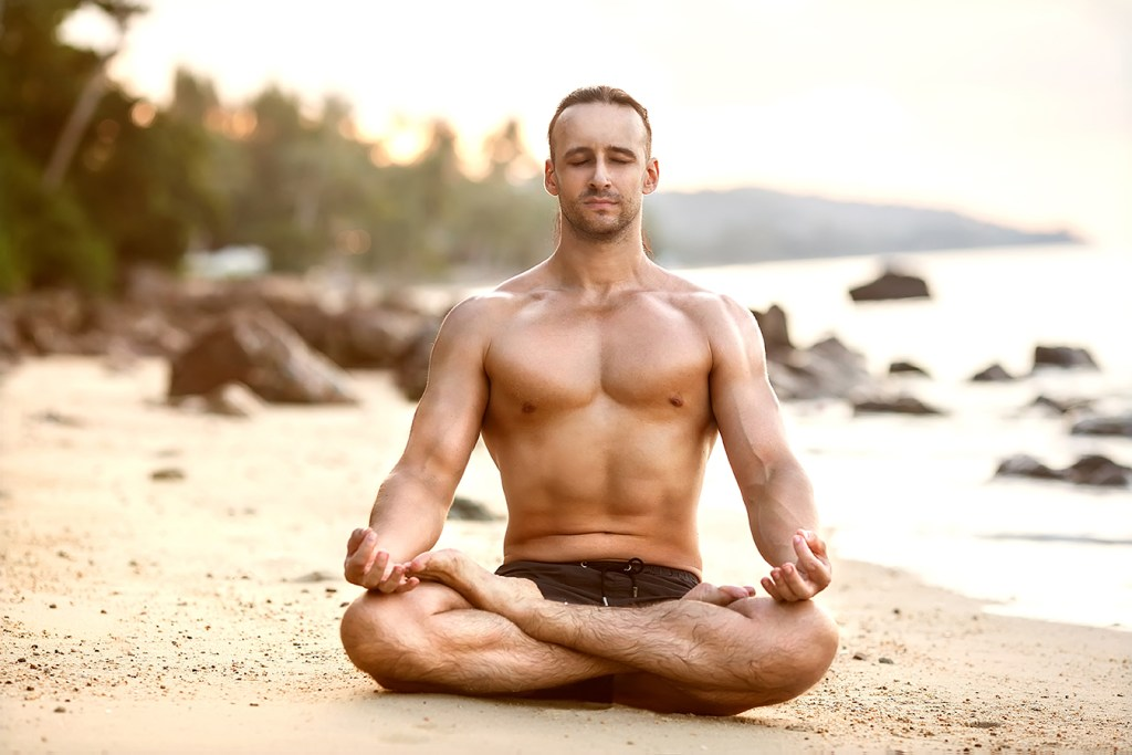 A man does yoga and meditation on the beach take a deep breath after experiencing difficult things.