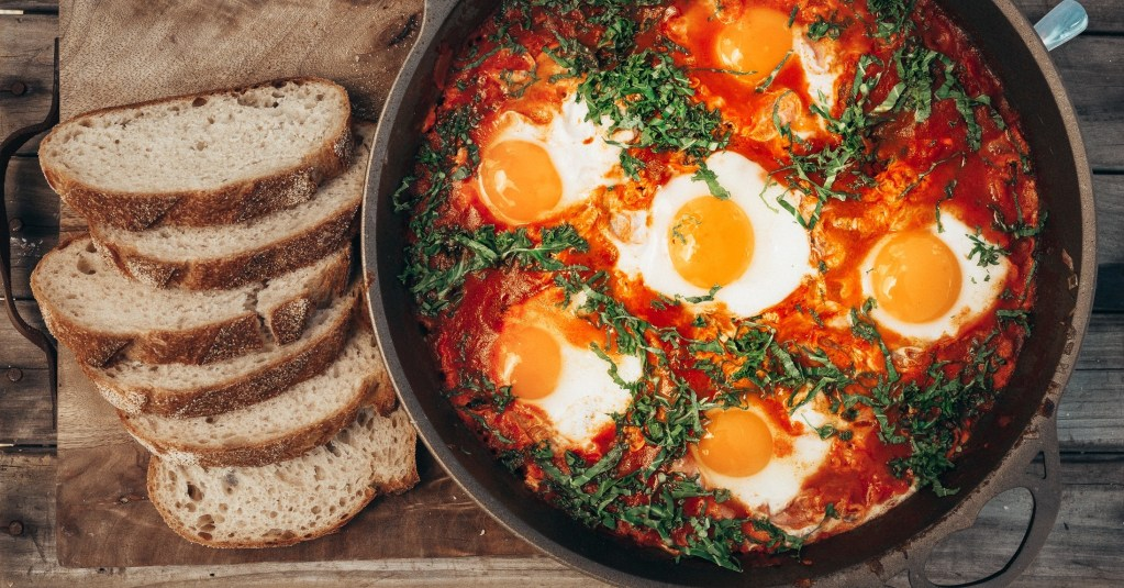 Shakshuka skillet of tomatoes ragu topped with herbs and served with bread.