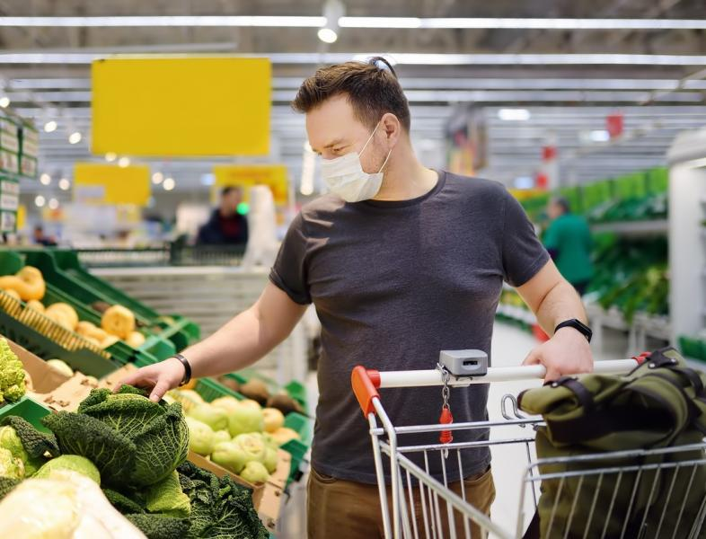 a man shops with a mask on, it's the new normal for the cornovirus