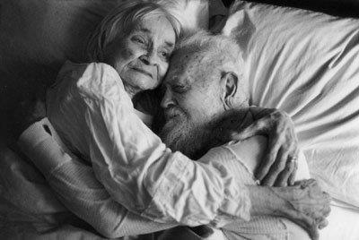 A senior couple in bed holding each other in love