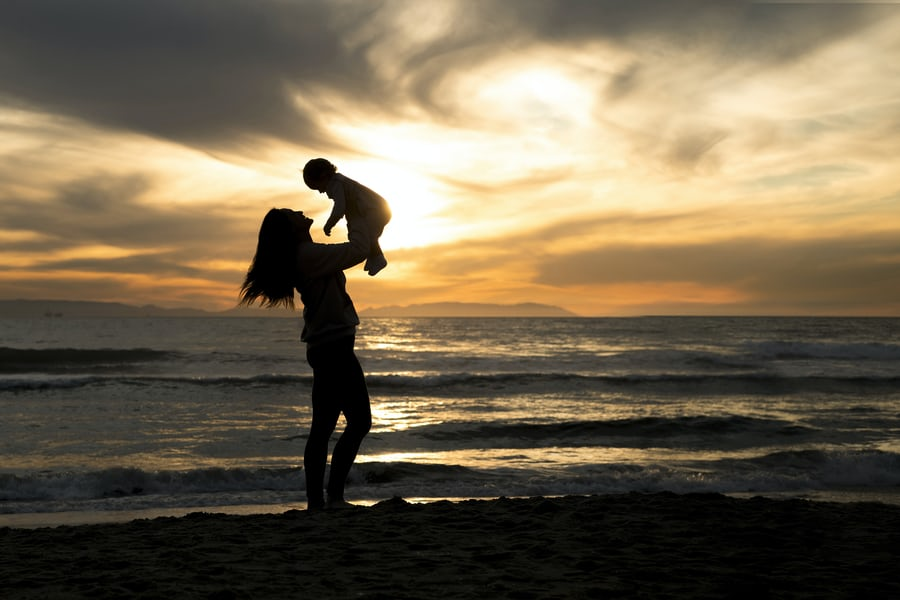 A mom holding her baby up in the air playing with him, they are on the beach with the sunset in the background