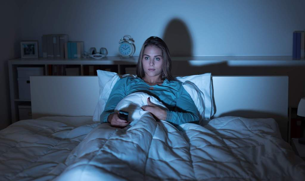 A woman watching tv at night because she can't sleep or isn't used to. She thinks she's not tired.