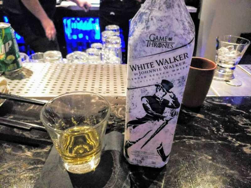 white bottle next to half full glass of whisky