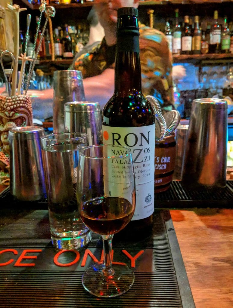 Rum on top of bar next to water glass in front of bottle