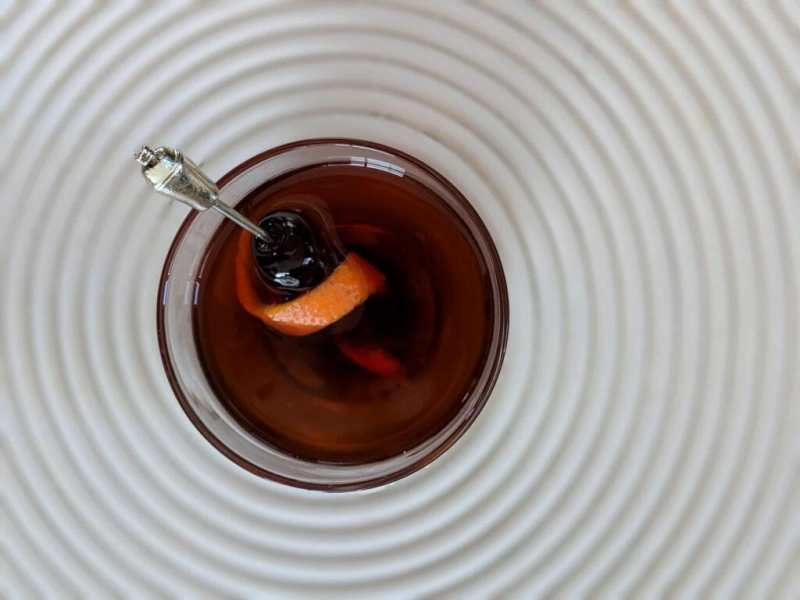 Glass in the middle of a spiral placemat shot from overhead with cherries and silver toothpick.