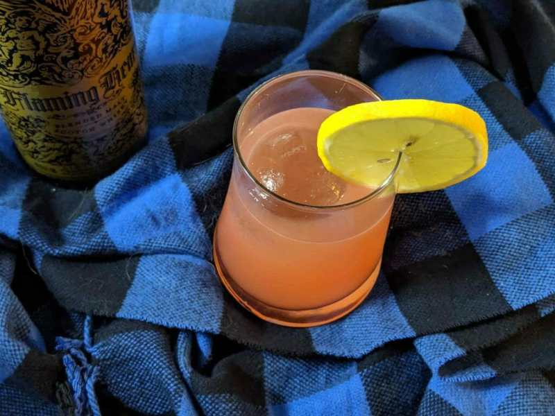 Cocktail in short glass with lemon wedge ontop of blue and black checkered cloth, next to whisky bottle