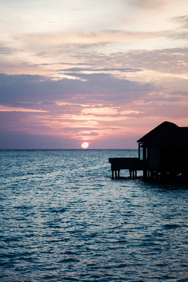 Purple sunset behind overwater villas