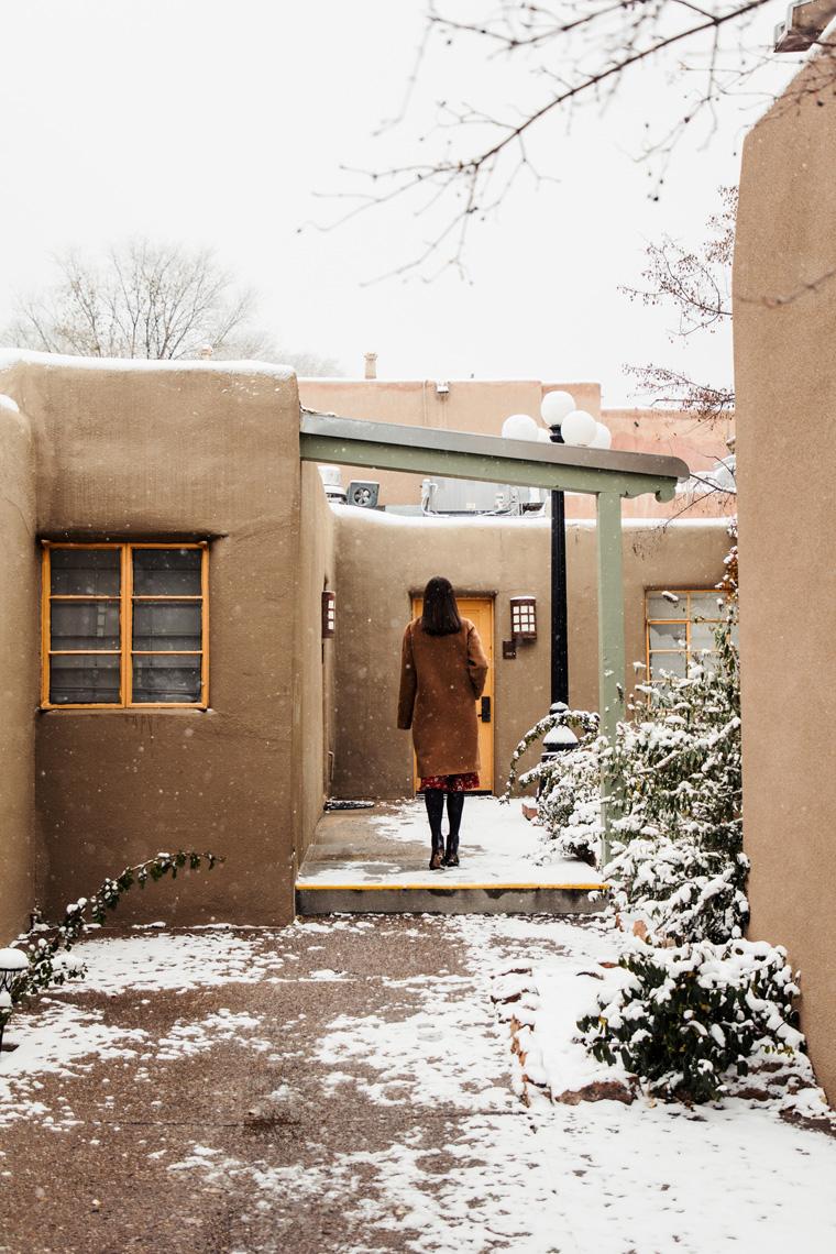 Carly walking through snowy La Posada de Santa Fe