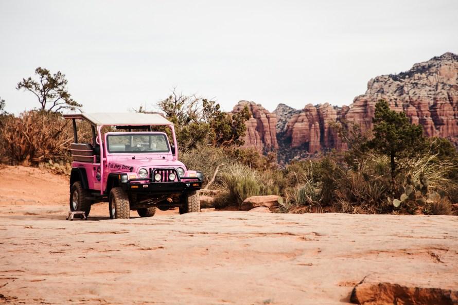 Pink jeep parked near red rocks