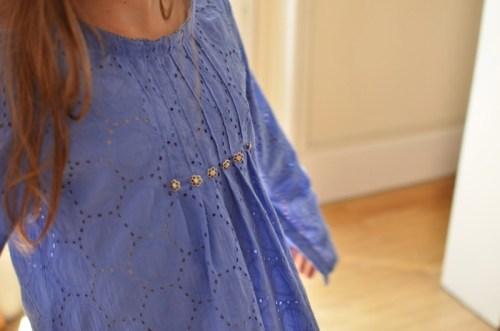 De beaux boutons en métal pour mettre en valeur les plis du devant de la robe
