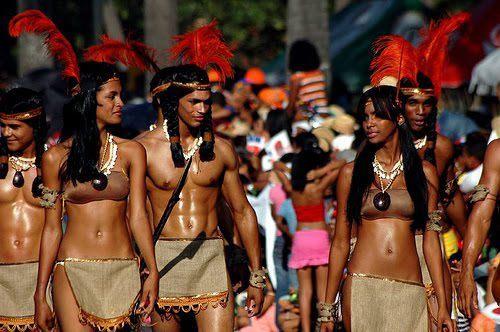 Un grupo de Tainos en vestido ceremonial, con un grupo más grande en ropa ordinaria detrás. Tienen piel morena y pelo oscuro, y los hombres llevan su pelo en trenzas. Sus ropas consisten de faldas cortas con accesorio de oro y ocre, y para las mujeres, bandeaus. Todos llevan puestos prendas hecho de caracoles.