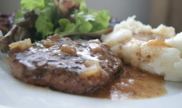 Salisbury steak with brown gravy served with mashed potatoes and green salad.