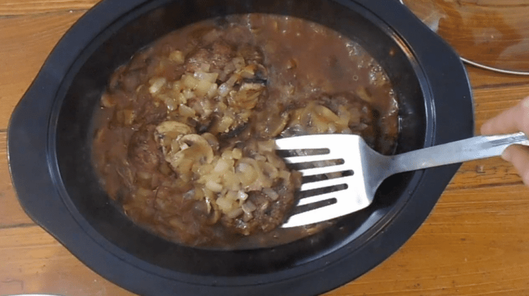 Cooked Salisbury Steak in a brown gravy with onions and mushrooms