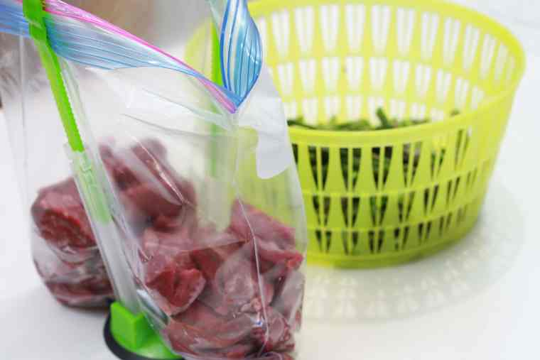 uncooked steak bites in a plastic bag, held up by green hands free baggie holder, with rinsed asparagusin a green basket.