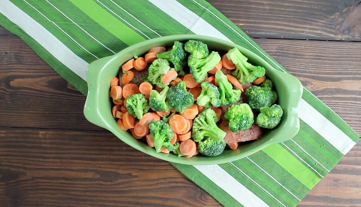 Easy one dish light and healthy salmon dinner prepared in a baking dish cooked over lemon slices then topped with broccoli and sliced carrots | 5dinners1hour.com
