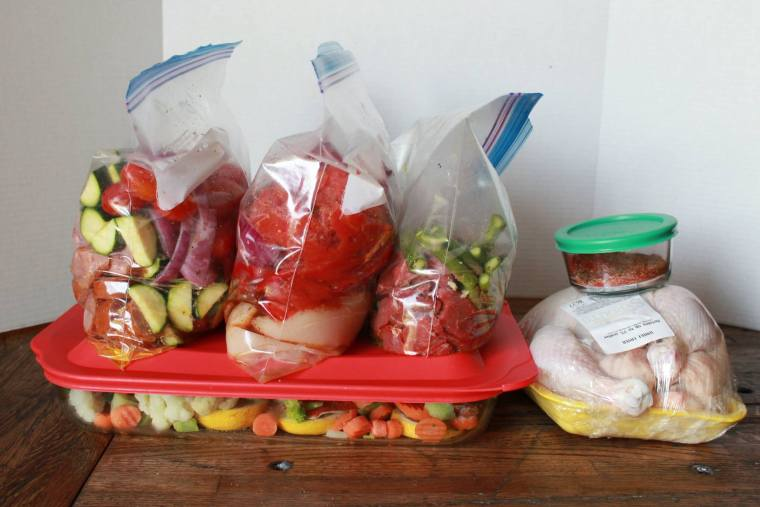 Three clear plastic bags meal prepped and to to cook sitting on top of another meal ready to be cooked along side of an cooked chicken all ready for the week.