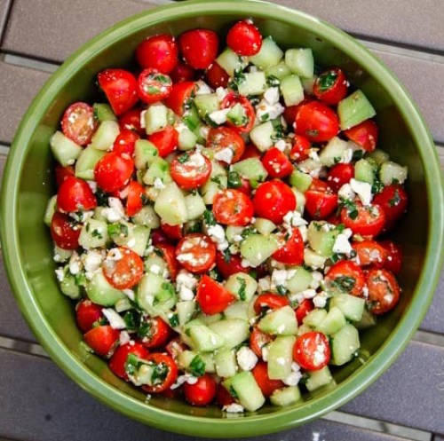 Cucumber, cherry tomatoes, mint and feta cheese all in bowl.